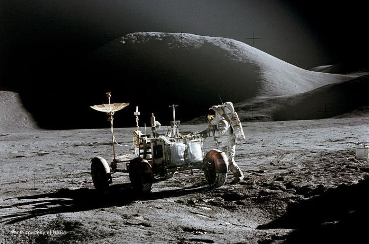 Apollo crew member posing with a rover in front of the Mons Hadley mountain on the Moon